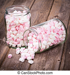Pink and white marshmallows spilling from a storage jar, over old wood background. Vintage effect with intentional vignette