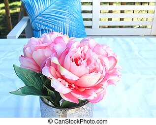 Pink and white peonies in a vase on a blue background