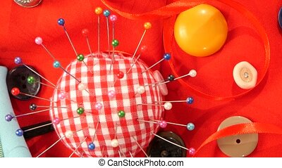 Cute pink and white pincushion with different buttons on red cloth