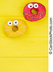 Pink and yellow donuts, top view.