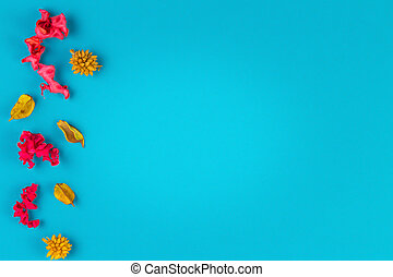 Pink and yellow dried flower plants border frame on blue background. Top view, flat lay.