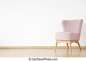 Pink armchair against white wall