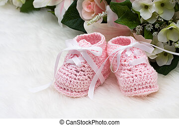 Pink Baby Booties - Baby booties with flowers sitting on a...