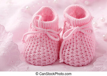 Pink baby booties on pink background