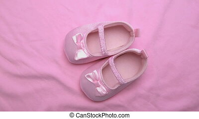 Pink baby booties on pink blanket