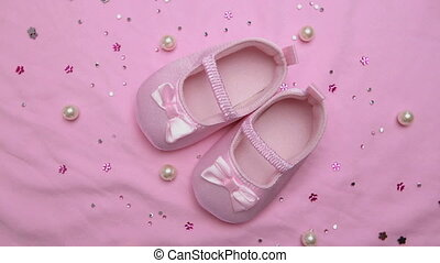 Pink baby booties on pink blanket with pearls revolving...