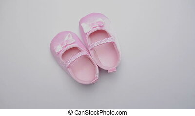 Pink baby booties on revolving white surface