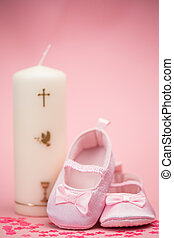Pink baby booties with christening candle on pink background
