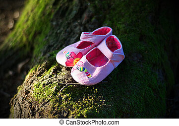 pink baby shoes in a green