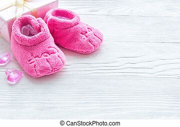 pink baby's bootees on wooden background