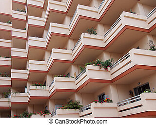 pink balconies on large modern apartment building with house plants