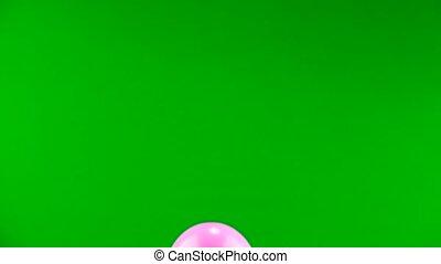 pink ball flies on the green screen