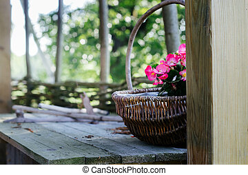 pink begonias in a wicker basket on wooden table outdoors- rural garden decoration