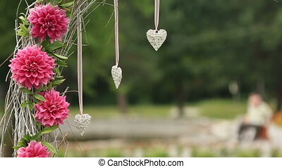 Pink beuatiful  flowers decorated with wicker hearts on a green background with texture