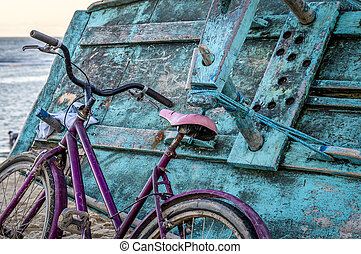 Pink bicycle leaned on turquoise fishermen boat