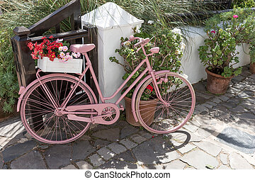 Pink bicycle with flowers on the walkway