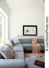 Pink blanket and pillows on grey corner couch in white living room interior with poster. Real photo