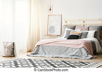 Pink blanket on grey bed in modern bedroom interior with poster and patterned carpet. Real photo