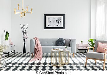 Pink blanket on grey sofa in living room interior with poster and patterned armchair. Real photo