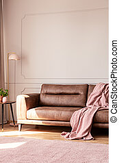 Pink blanket on leather couch in white living room interior with lamp and plant on table. Real photo