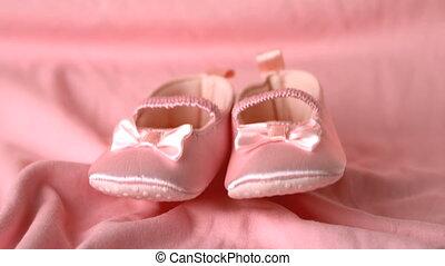 Pink booties falling on pink blanket in slow motion