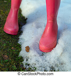Pink boots on the snow and grass