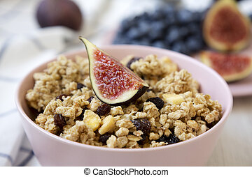 Pink bowl of fruit granola with fruits ready to eat, side view. Close-up.