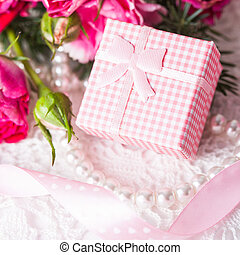 Pink box with little present and flowers