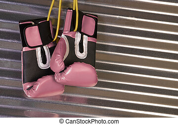 Pink Boxing Gloves Hanging on a Hook - Boxing gear stored...
