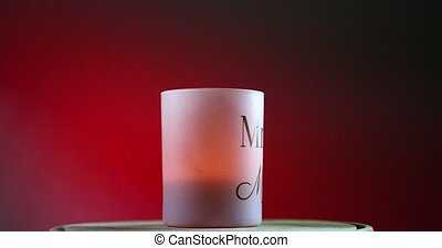 Pink burning candle on red gradient background rotates on the wooden platform