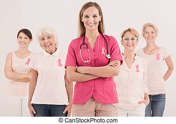 Pink cancer awareness ribbons - Happy women and doctor with...