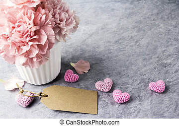 Pink carnation flower in white cup with blank brown paper tag and heart