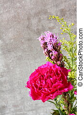 Pink carnation flower on rustic wooden background