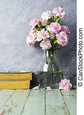Pink carnation flowers in clear bottle on old wood