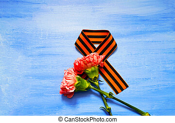 Pink Carnation with St. George ribbon on blue background, symbol of the great Victory, symbol of world war II.
