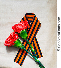 Pink Carnation with St. George ribbon on craft background, symbol of the great Victory, symbol of world war II.