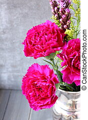 Pink carnations flower bouquet in metal vase on rustic wooden background