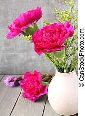 Pink carnations flower bouquet in vase on rustic wooden background