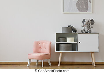 Pink chair next to white shelf with boxes and plush toy in...