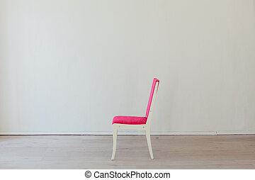 pink chair stands alone in the white room