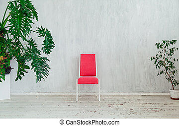 pink chair with home plants in the interior of a vintage gray room