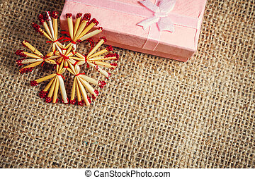 Pink christmas gift on burlap background, close up