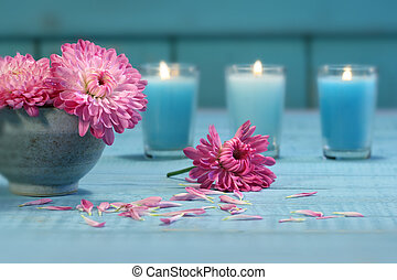 Pink chrysanthemum flowers in bowl of water with candles