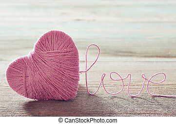 "Pink clew in shape of heart and word ""love""on vintage wooden background"