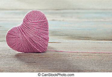 Pink clew in shape of heart on vintage wooden background