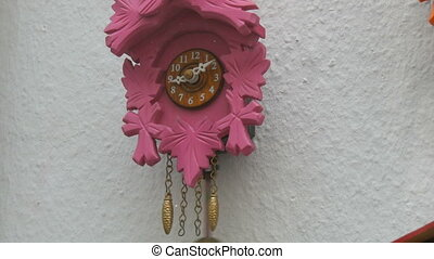 Pink clocks wall clock with a pendulum in the window of a watch shop.