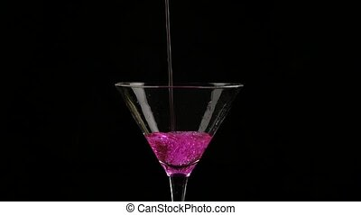 pink cocktail poured into a glass on a dark background. slow...