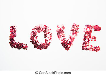 Pink confetti spelling out love on white background