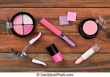 Pink cosmetics on wooden background.
