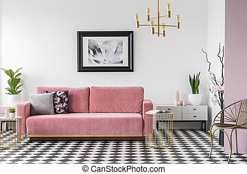 Pink couch next to cabinet with plant in living room interior with poster and armchair. Real photo